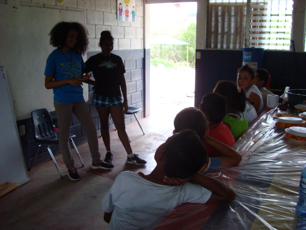 Lorena Feliz (curly hair) and clytie, giving the students a demonstration of the fruits and veggies that will be planted in the garden.