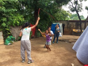 Students playing jump rope with their host families.