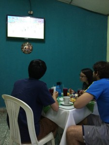 Sean, Crystal, and Bryan watch a futbol match on TV during our last dinner at Buffet Estelí.