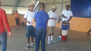 Robert, Rashid, and Malcom learning to play traditional Dominican instruments before they can dance with the women.