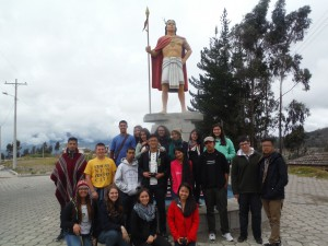 The group in front of a statue of an indigenous man
